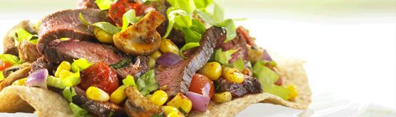 With lean grilled beef and market-fresh veggies, this crispy crunchy main-course salad has all the satisfaction of a nacho platter with a fraction of the fat and a BIG boost of nutrients. Using oven-toasted whole wheat flour tortillas as the tostada base is a healthier choice than traditional fried corn tortillas. #CanadianBeef #Steak