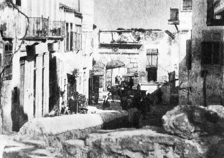 """Χανιά. Το βόρειο τμήμα της σημερινής οδού Δασκαλογιάννη του 1918-20. Ανθρωποι μπροστά στα μικρά αλλά ζωντανά μαγαζάκια, ο μεγαλοπρεπής πυλώνας που οδηγούσε στην προκυμαία (γκρεμίστηκε το 1949) και η """"ανισόπεδη διάβαση"""" πάνω απ' τη γέφυρα που διέσχιζε το δρομάκο που ήταν στη θέση της βυζαντινής τάφρου. Φωτογραφικό Αρχείο Μανώλη Μανούσακα από την έκθεση: ´ΧΑΝΙΑ-ΒΕΝΕΤΙΑ χθες και σήμερα´"""