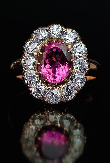 An Antique Diamond and Pink Tourmaline Cluster Ring circa 1900 The gold ring is centered with a purplish pink tourmaline (approximately 2 ct) framed by twelve old European cut diamonds (H-I color, VS1-SI1 clarity) with an estimated total weight of 2 carats.