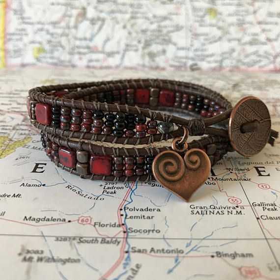 This is a 2-wrap bracelet made with 6mm CzechMates Tiles in Picasso Coral Red, accented with 8mm Picasso Red seed beads and 8mm black seed beads in a geometric design, and copper-toned metal beads. The button closure is a copper-toned leaf pattern and the charm is a copper-toned