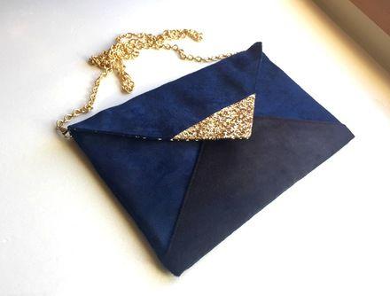Sac pochette de soirée  graphique bleu marine et noir en suédine avec chaîne dorée amovible au style chic et épuré.  La pointe du rabat est recouverte de tissu à paillette - 19293511
