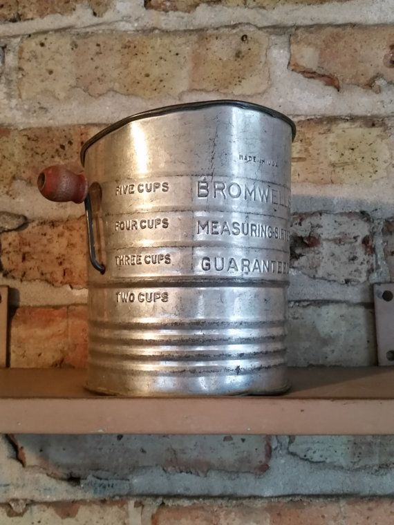 This neat vintage Bromwells hand crank sifter / measuring cup would make an awesome piece of rustic kitchen decor. This particular metal handheld flour sifter appears to be made from tin and has a wood handle unlike the plastic handles found on the midcentury versions. Crank operated flour sifter is marked Bromwells Measuring-Sifter Guaranteed without a patent number. Believed to be from the 1940s. DIMENSIONS 6 height 5 at base   ----  All items listed are from my grandparents estate. B...