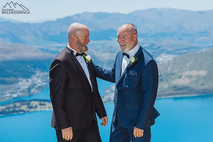 Same sex wedding, two Grooms stand above Lake Wakatipu on the Ledge in summer wedding