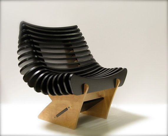 BLACK RIBS ARE SLOTTED AND HELD BY GRAVITY. SINCE THEY ARE NOT PERMANENTLY FIXED THIS ALLOWS THE USER TO TAKE THEM OUT AND PUT BACK IN ANOTHER ORDER TO MAKE A DIFFERENT SHAPE AND CONTOUR.