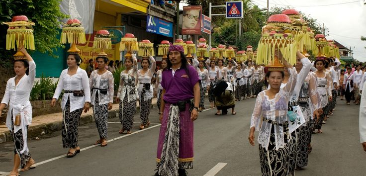 Dressed in traditional costume, a parade of women gracefully carrying offerings on their head, lead a procession in Ngaben, the Balinese cremation ceremony