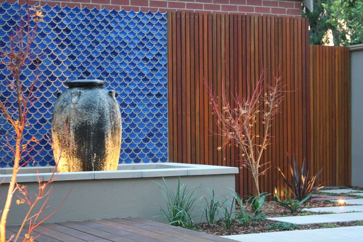 A newly built Courtyard garden featuring these  georgeous blue fish scale tiles as a backdrop to a water feature pot.Garden design by RPGD www.rpgardendesign.com.au
