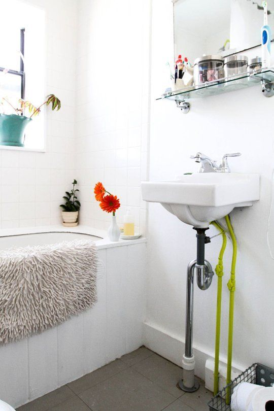 neon-painted pipes in a simple white bathroom