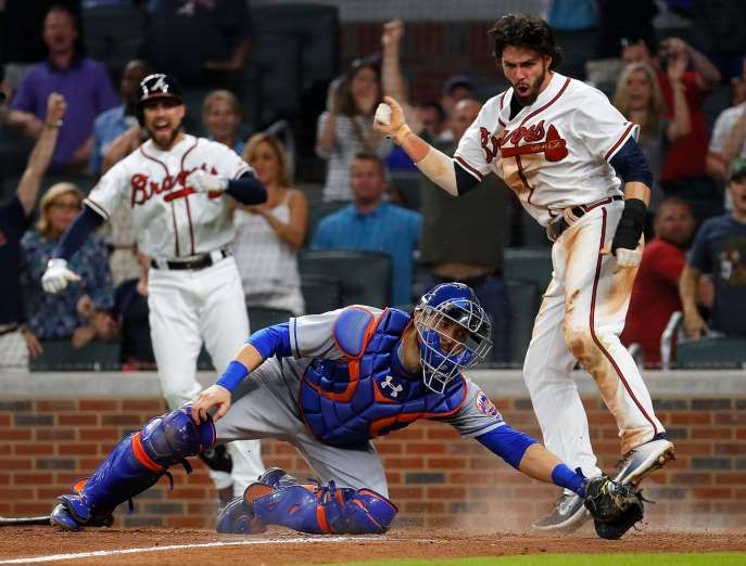 BEATEN:    Dansby Swanson, right, of the Braves scores the game-winning run as he slides past Travis d'Arnaud of the Mets on a RBI hit by Rio Ruiz on June 9 in Georgia. The Braves won 3-2.