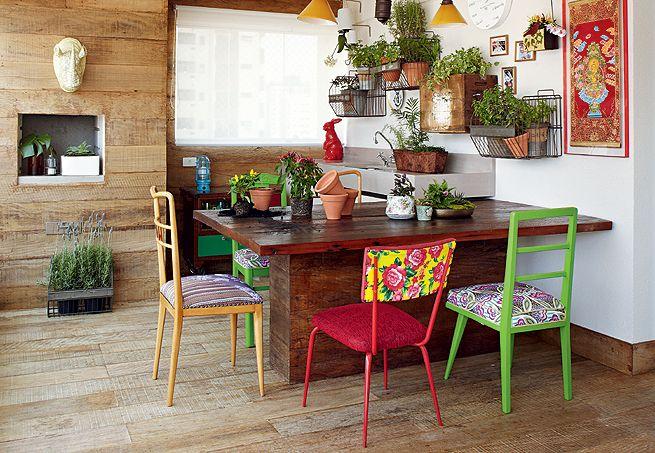 Do outro lado da varanda gourmet, a mesa de madeira ganha um toque mais alegre com as cadeiras coloridas, que têm estilos diferentes