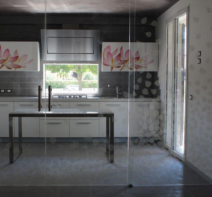 Vetrata scorrevole progettata per Cristal con vere foglie di Buddha disposte manualmente e poste fra due vetri saldati ad alte temperature. Cucina laccata progettata per arredo privato con pensili decorati.