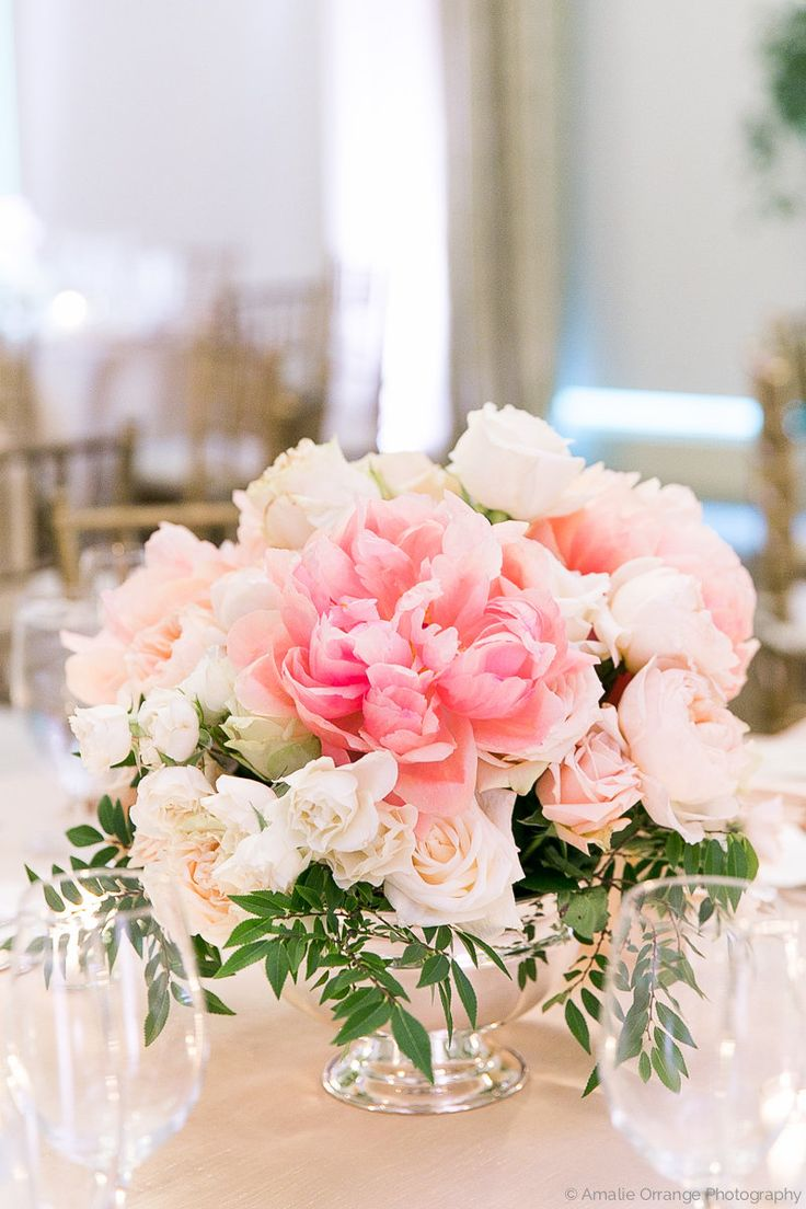 a lush spring time wedding table arrangement of faded coral charm peony, peach juliet garden rose, garden spirit rose, white majolik spray rose, vendela rose, sarhara rose, elm and bay leaf in a classic silver revere bowl.