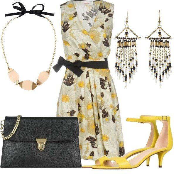 Outfit composto da abito floreale con scollo incrociato, sandali con tacco comodo, e clutch con chiusura a scatto. Completano il look la collana ad effetto dorato e gli orecchini pendenti.