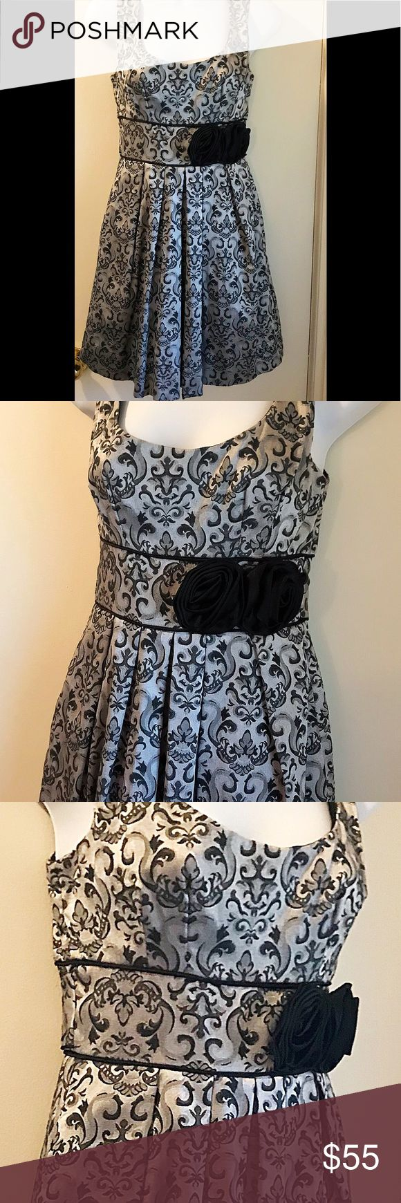 Speechless Occasion Dress Gorgeous dress in a metallic silver and black detailed pattern. Complimented with black satin rose detail and tie back. Great dress for any special occasion.  Sz 3 51% Cotton 46% Polyester  3% Spandex  109-18 Speechless Dresses