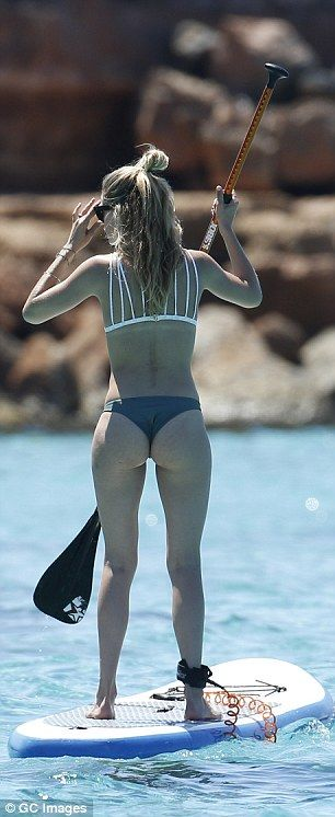 Her white triangle bikini top featured multi-back straps and she matched it with a grey thong which showed off her pert posterior to perfection.