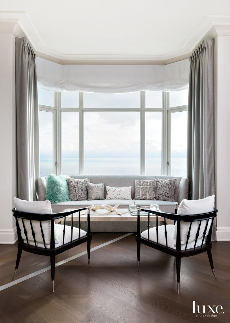 Interior Designer Anthony Michael had a sofa custom-made to fit into the living room bay window of this Chicago residence, giving homeowner Judi Simms a cozy place to curl up with a book. The sofa joins chairs by Schnadig International Corporation and a Bernhardt coffee table.