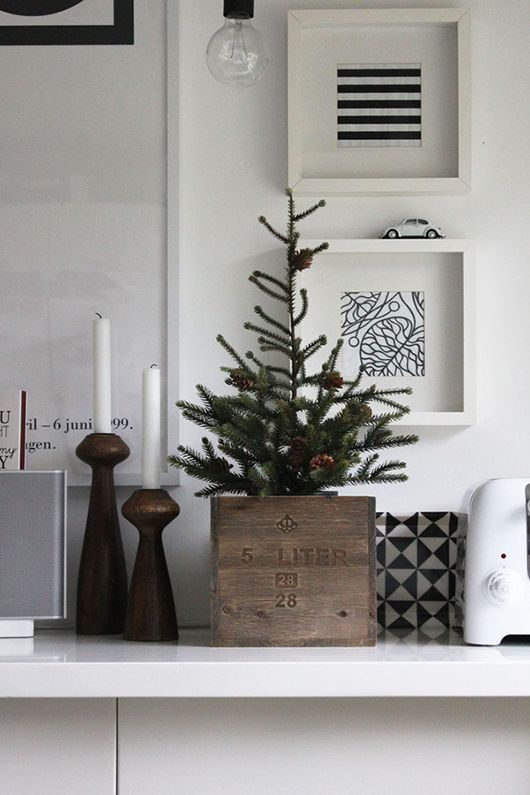 tiny tree in a small crate, wooden candlesticks with white tapers