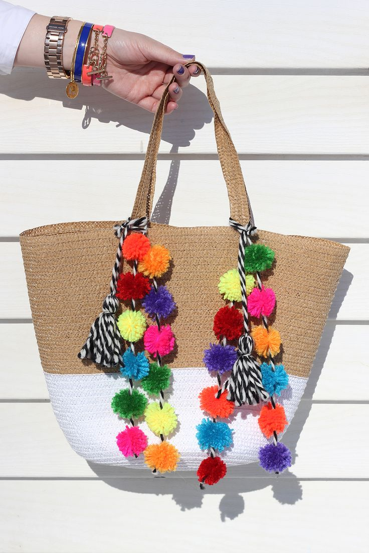 Add colorful strands of neon pom poms to this dollar-section straw tote to dress up your beach day look.