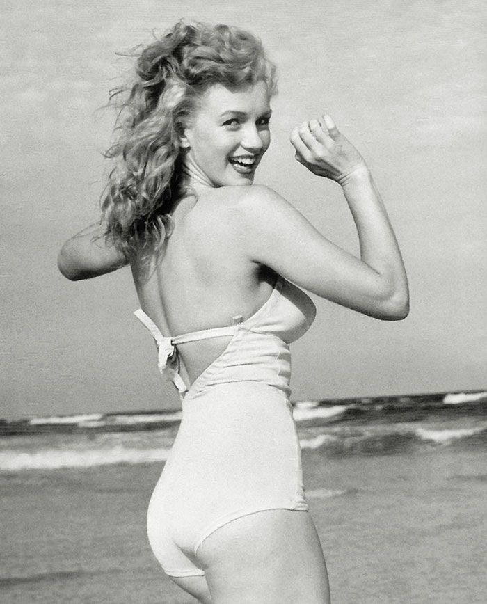 A young Marilyn Monroe is a picture of joy in a white one-piece bathing suit (Circa 1945)