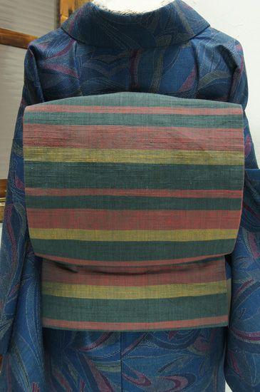 赤、黄、緑で織り出された木綿紬のリバーシブル帯です。