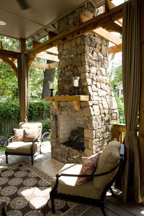 This outdoor fireplace and patio would fit prefectly under a deck. The use of tile instead of poured concrete gives the feeling that this is not simple a patio fitted under the main deck but rather a bonifide outdoor room, with a fireplace, cozy furniture, accessories and a proper floor. In other words, it has everything other rooms have, except windows and doors.~EBM