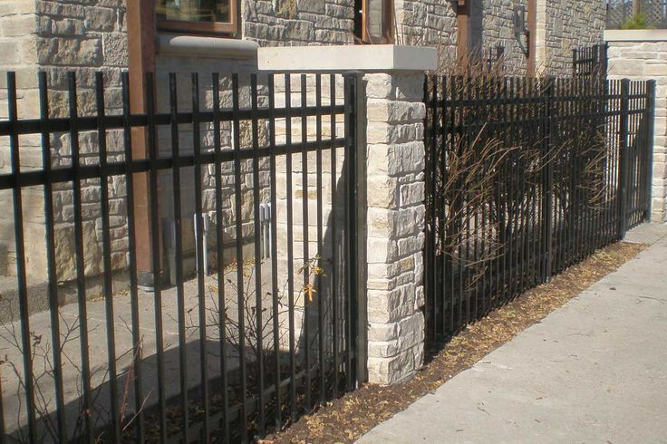 Photo of industrial plugged spear top residential Ultra aluminum fence with masonry pillars. Designed and installed by First Fence Company in Hillside, IL.