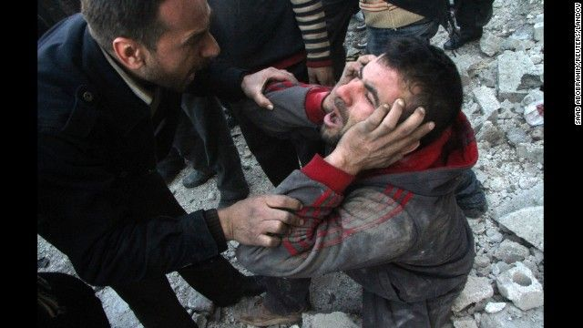 A man reacts after what activists said was an air raid by forces loyal to Syrian President Bashar al-Assad in the al-Marja district of Alepp...