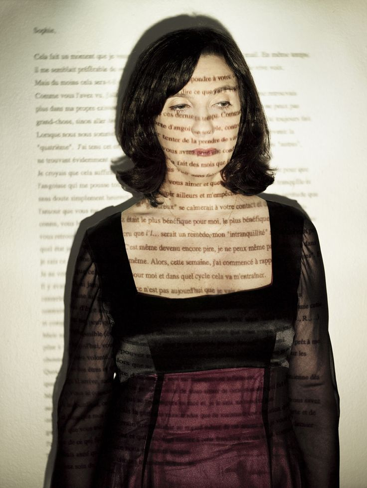 Sophie Calle - Portrait photo of herself covered with a projection of text written in her language, giving it a personal aura