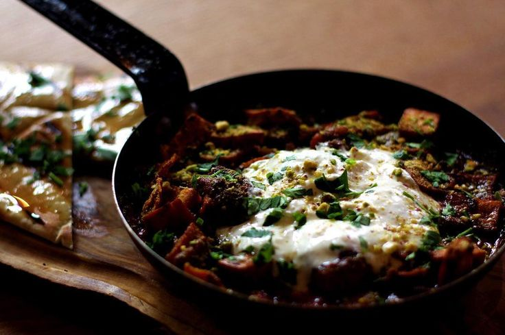 Lamb kofta -- a deconstructed kebab, baked in a pan in a chunky home-made tomato sauce (with plenty of herbed pita chips.) Topped with yogurt and crushed pistachios.