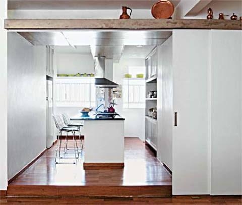 Portas de correr de MDF e revestidas de laminado texturizado parecem uma extensão da parede que separa a cozinha da sala. A ilha, com fogão e pia, domina o centro. Foram feitos nichos de gesso acartonado para encaixar a geladeira e o armário. O piso é de madeira, mas, perto das áreas de trabalho, para facilitar a limpeza, foi feito um recorte e aplicado cimento queimado vermelho. Projeto de Diana Malzoni.