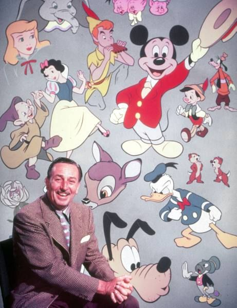 Movie studio head Walt Disney sitting in front of backdrop filled w. Disney creations including Pluto, Goofy, Peter Pan, Pinocchio, Bambi, Snow White & Dopey.