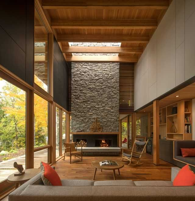Tall wood living room with a fireplace clad with locally sourced granite in a woodland retreat located along the shores of Contau Lake, Haliburton County, Ontario, Canada [2364×2432] - Imgur