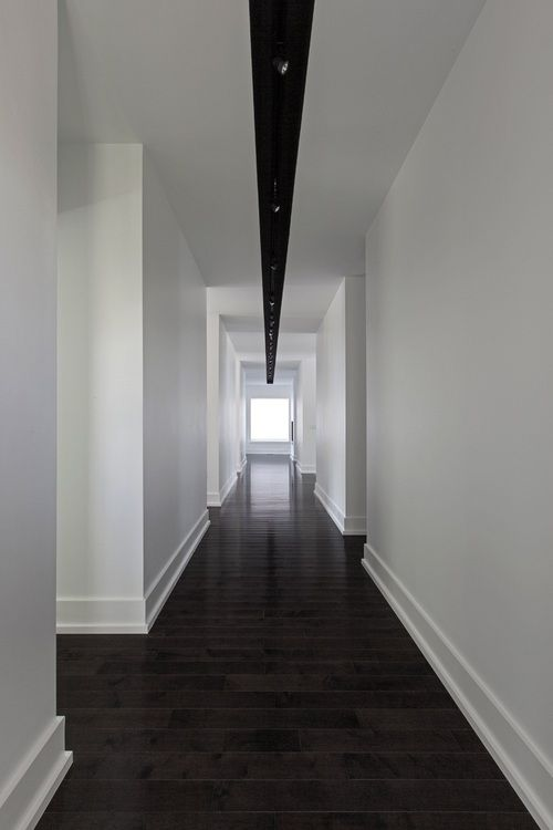 Detailed skirting boards formalize the contrast of dark floor and white walls --- not sure what light fitting is achieving!!