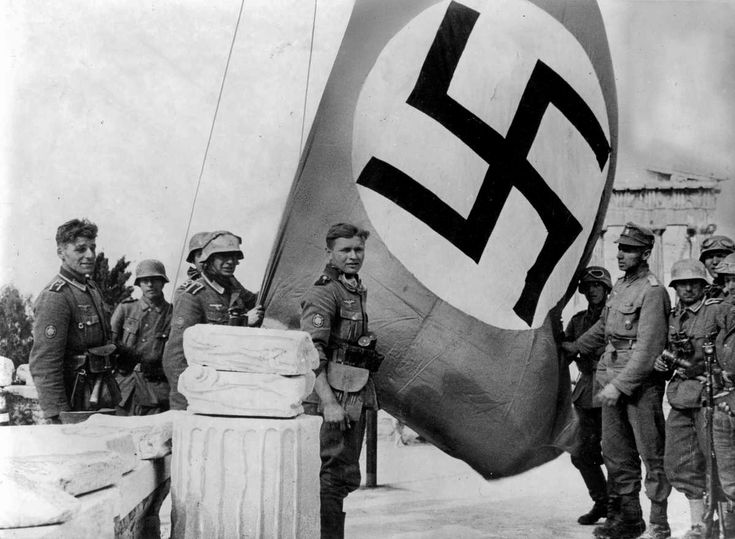 German mountain troops raise the swastika on the Sacred Rock of the Acropolis, Athens, Greece, April 1941. The Parthenon is partially visible behind the flag. The troops wear winter uniforms that do not go well with Greek warm spring weather.