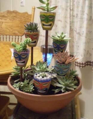 Never seen a string of  Tiki lights like this, so I'm thinking the minature clay pots with drawings or felt appliques since the succulents can stay inside