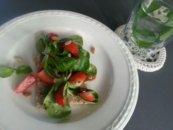 Speltcracker met bladsla aardbei pijnboompit pompoenpit en balsamico - azijn sinaasappel munt dressing