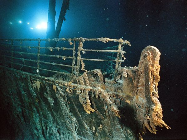 The Mir 1 submersible illuminates the bow railing of the Titanic.