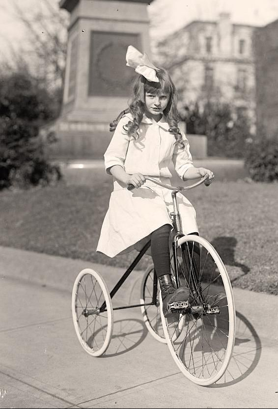 Awesome tricycle! I just love the way she is dressed. And I love the big bow on her head.