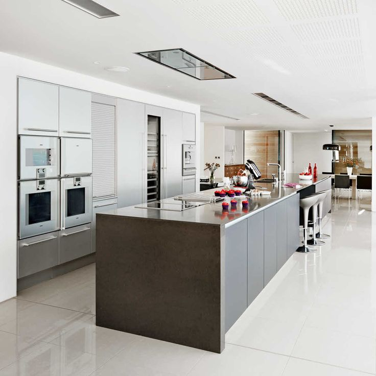A central wall running parallel with the island unit that contains four ovens, fridge, freezer, wine cooler and cabinets