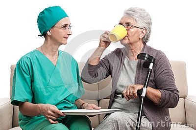 Home visit. A female doctor giving a cup of tea to an old disabled woman. Senior taking pills. Isolated on white.