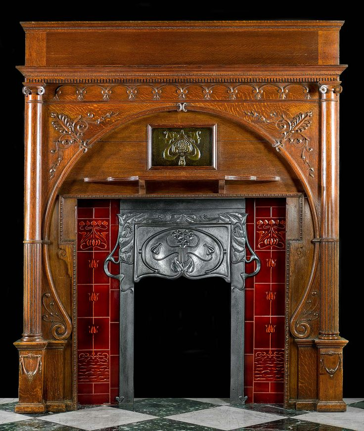 An exceptional and rare carved oak Art Nouveau chimneypiece with an integral decorative cast iron hooded insert set between two red tiled panels beneath the centred embossed copper plaque. The carved athemion detail echoed on the insert and tiles, together with the graceful sweep of the arch framing the opening, flanked by twin slim reeded columns, is very typical of the designs of this period. English, circa 1900.
