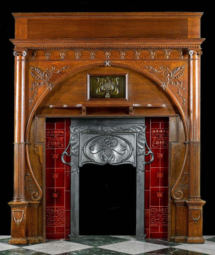 Chimenea de roble tallada excepcional y rara art nouveau con un inserto de hierro fundido con capucha decorativa integrada situada entre dos paneles de tejas rojas debajo de la placa de cobre repujado centrada. Inglaterra, c.1900.