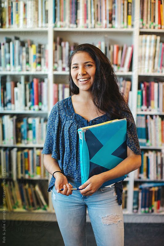 Portrait of happy high school teenage girl holding book binder in library by Rob and Julia Campbell