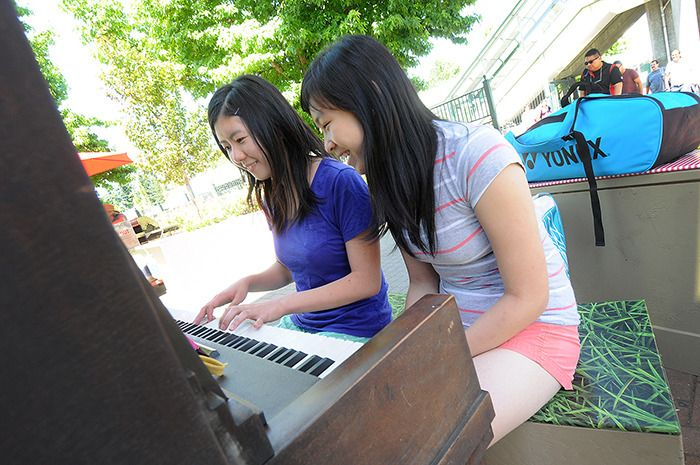 Alison Wu (left) and Stella So play a piano at the Surrey Central SkyTrain Station in 2014.