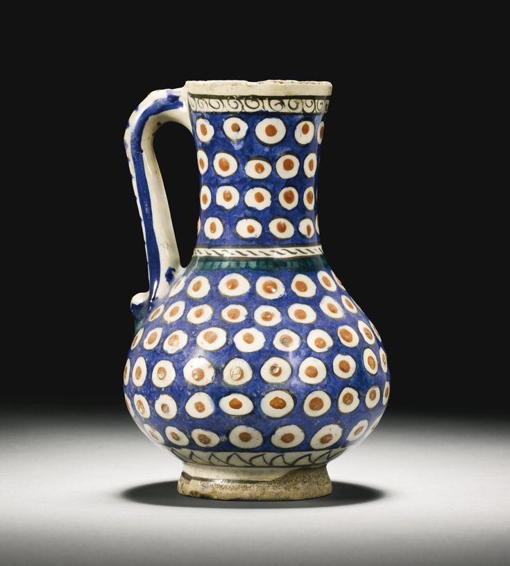 AN IZNIK POLYCHROME POTTERY JUG, TURKEY, CIRCA 1600 of baluster form with a cylindrical, slightly flaring neck and curved handle, painted with an overall pattern of circles with a black outline and relief red spot against an underglaze cobalt blue background, the shoulder with a band of curved black lines and a petalled green fringe, the handle with cobalt blue stripes and a green splash on body