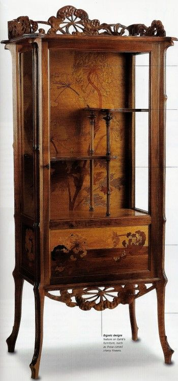 Walnut vitrine featuring organic motifs, marquetry, and floral influences.