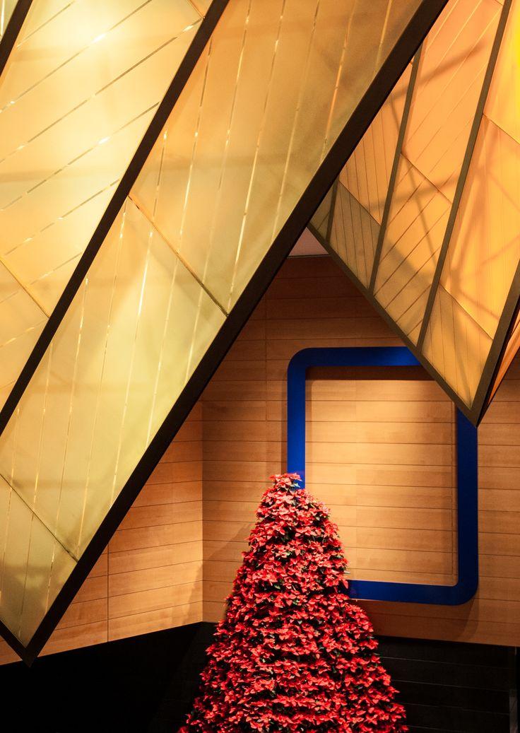 A bold red tree reaches upward toward inverted pyramids making for a dramatic entrance in the Grand Hyatt Berlin lobby. #LivingGrand | Grand Hyatt
