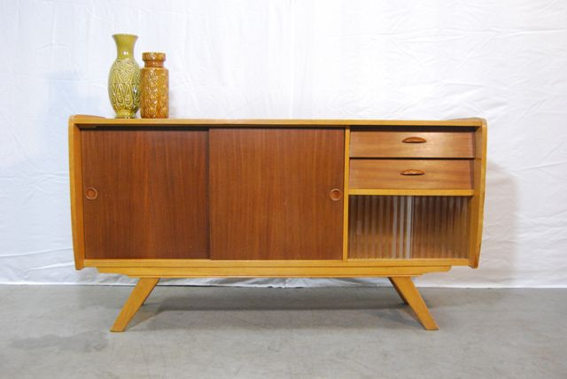SOLD / Eigentijds compact dressoir uit de jaren 50 met twee kleuren houtfineer en geslepen glazen ruitjes. De wandkast staat op eigenwijze taps toelopende schuine poten met een mooi onderranddetail.