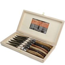 A boxed set of six traditional Laguiole steak knives.  Made in Thiers, an ancient town in central France famous for its cutlery industry. Because Laguiole describes a style of knife, and is not a brand name, Laguiole cutlery and knives are now being made all over the world. So we were very happy to find these, which are still made in France, by the same company that first started making them in 1920.  Sharp stainless steel blades with handles made from assorted European hardwoods.    Made…