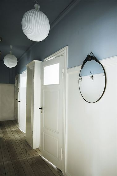 30's nostalgia, preserving the windows at the top of the original doors. blue wall colour at top of walls adds interest, while the white keeps the hallway from being a long dark space.  round white ceilng lights