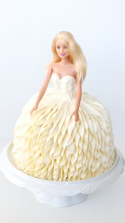 "Recipe with video instructions: You can say, ""Yes!"" to this gorgeous wedding dress cake modeled after Vera Wang's Liesel gown. Ingredients: Cake Batter:, 1 ½ cups unsalted butter, room temperature, 3 cups granulated sugar, 3 tsp vanilla extract, 6 large eggs, 6 cups all-purpose flour, 3 tbsp + 1 ½ tsp baking powder, 3 cups milk, 1 ½ tsp salt, white food colouring (optional), 1 barbie doll, Buttercream (recipe at www.pankobunny.com)"